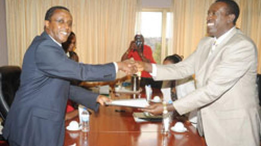 Dr Biruta (L) hands over to his successor Dr  Ntawukuliryayo at the Parliament Buildings yesterday. The New Times / John Mbanda.
