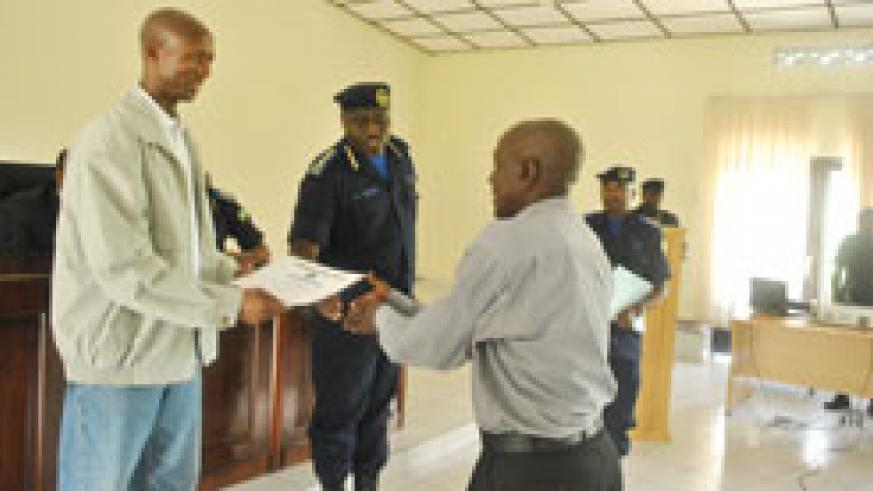 The Minister of Internal Security, Sheik Musa Fazil Harerimana, presents a certificate of service to a retired police officer. On his left is Police boss Emmanuel Gasana