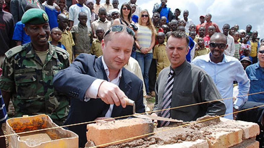 Oleg Moiseev, the MD of Rogi, a mining company that is exploring gold in the Northern Province, lays a brick at a school construction site in Burera District yesterday. The firm donated Rwf6 million to two schools towards the construction of extra classro