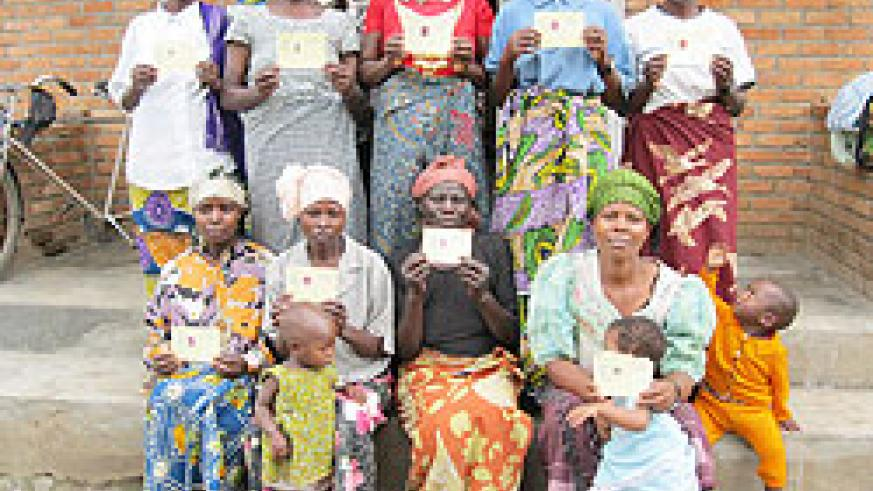 Some of the beneficiaries of the free health insurance with their cards . The New Times / B Mukombozi.