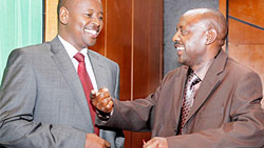 Local Government Minister James Musoni (L)chats with Hon Abbas Mukama before the session to discuss VUP Umurenge yesterday. The New Times T. Kisambira.