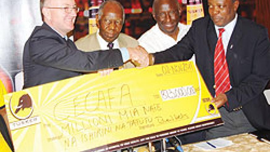 Serengeti Breweries Managing Director Richard Wells (R) hands over the cheque to Cecafa officials yesterday. The New Times/B. Mugabe.
