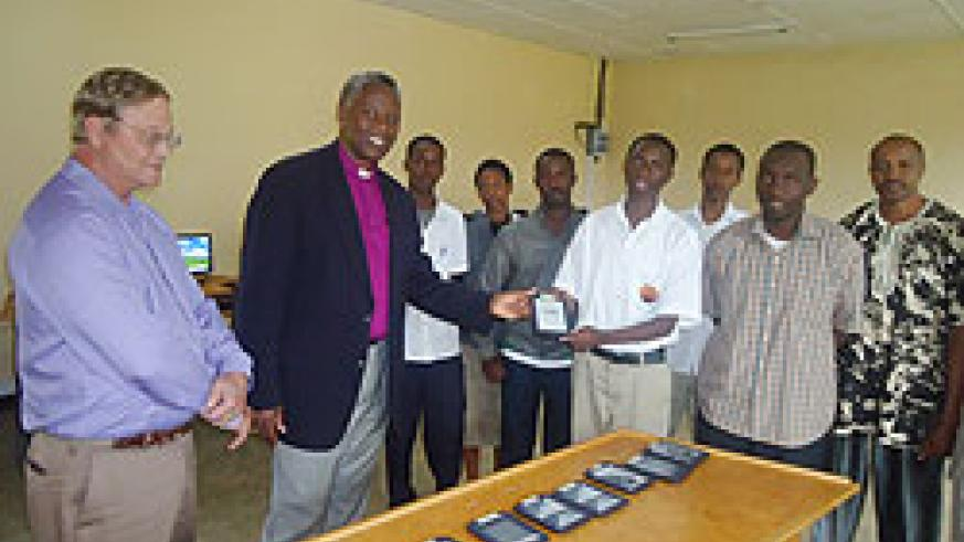 Bishop Laurent Mbanda hands over one of the Nooks hand set digital readers to students as Rwanda Leadership Foundation boss Gaylord Layton (L) looks on. The New Times / B. Mukombozi