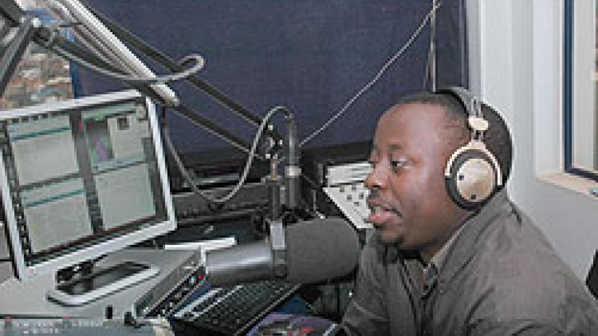 A broadcast journalist airs news in a radio studio. Government says it would woo  investors to the media industry. The New Times / File.