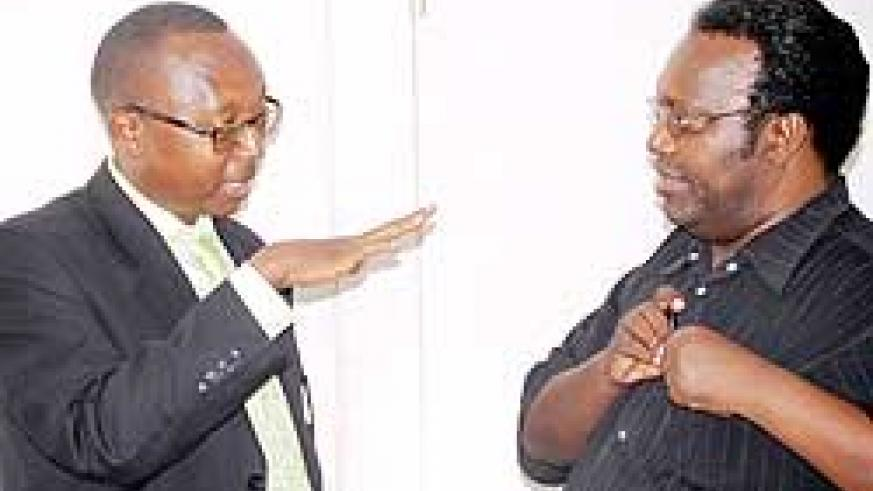 Auditor General Obadia Biraro (L) converses with Public Accounts Committee Chairman Juvenal Nkusi yesterday. The New Times / John Mbanda