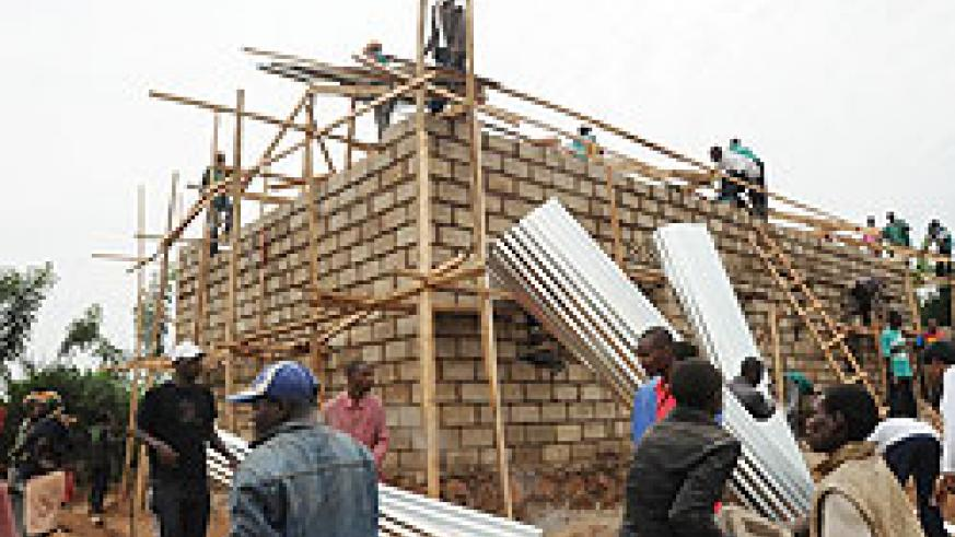 People offer help to put up a house belonging to a poor family during the campaign against grassthatched houses. The New Times / File