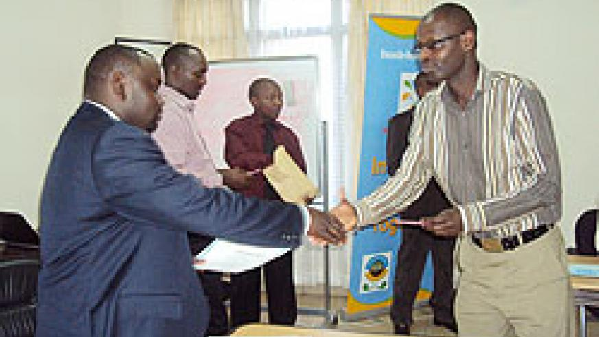 Kigali City Vice Mayor, Alphonse Nizeyimana (L),  hands a certificate to a trainee.The New Times / JP Bucyensenge.