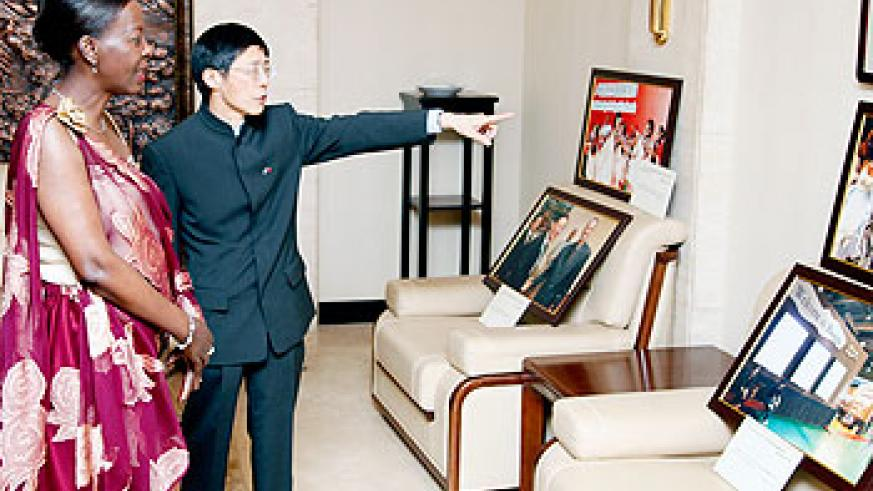 Chinese Ambassador to Rwanda Shu Zhan guides the Foreign Affairs Minister, Louise Mushikiwabo, to an art exhibition room.The New Times/ Timothy Kisambira.