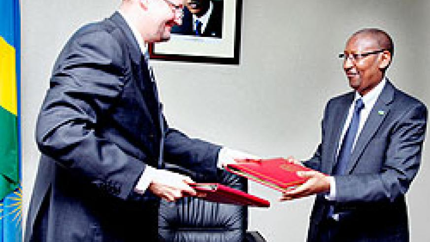 Ambassador Michel Arrion (L) exchanges documents with John Rwangombwa Minister of Finance yesterday. The New Times / Timothy Kisambira.