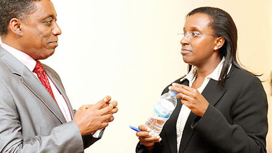 Desta Mebratu, Deputy Regional Director of UNEP (L) chats with Caroline Kayonga, PS in the Natural Resources ministry at the meeting yesterday. The New Times / T. Kisambira.