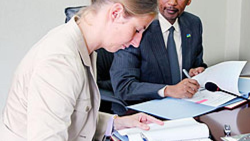Dr. Daniela Beckmann the Director of Germany Development, ( L) together with Minister John Rwangombwa, signing a grant agreement yesterday. The New Times / Timothy Kisambira.