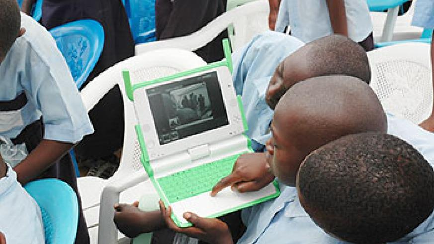 Kagugu Primary School boys try to take photographs with one of the Lap tops given to them. The New Times/J. Mbanda