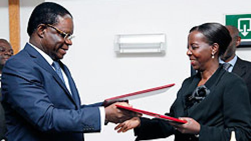 Basile Ikouebe (L), the Minister of Foreign affairs of Congo, exchanges documents with his Rwandan counterpart Louise Mushikiwabo after their meeting. The New Times / T. Kisambira