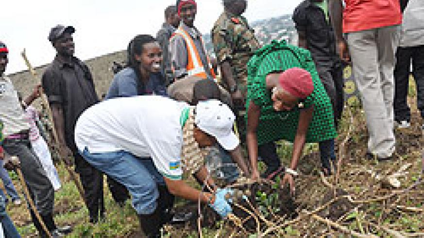 Dr. Rose Mukankomeje (L), Director General of REMA plants a tree with local residents yesterday in Rubavu.The New Times / Alex Ngarambe.