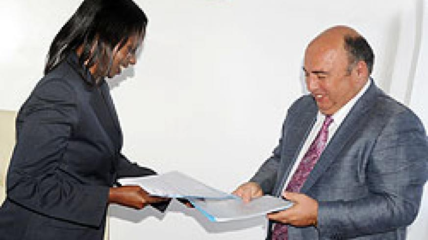 State Minister in charge of Energy and Water Emma Francoise Isumbingabo (L) and HAKAN Chairman Ahmet Karasoy exchange documents after the signing. The New Times / J. Mbanda.