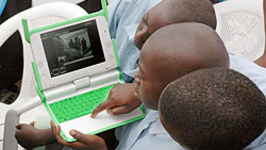 Primary School boys with a laptop. A pastor is being held in connection with theft of such laptops. The New Times / File.