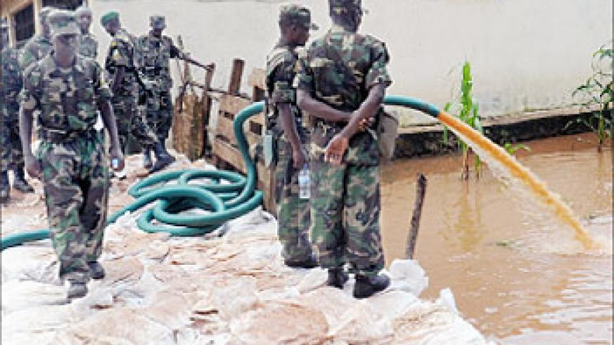 RDF soldiers take part in an exercise to drain flood waters  in Nyabugogo  on Sunday. The New Times / File.