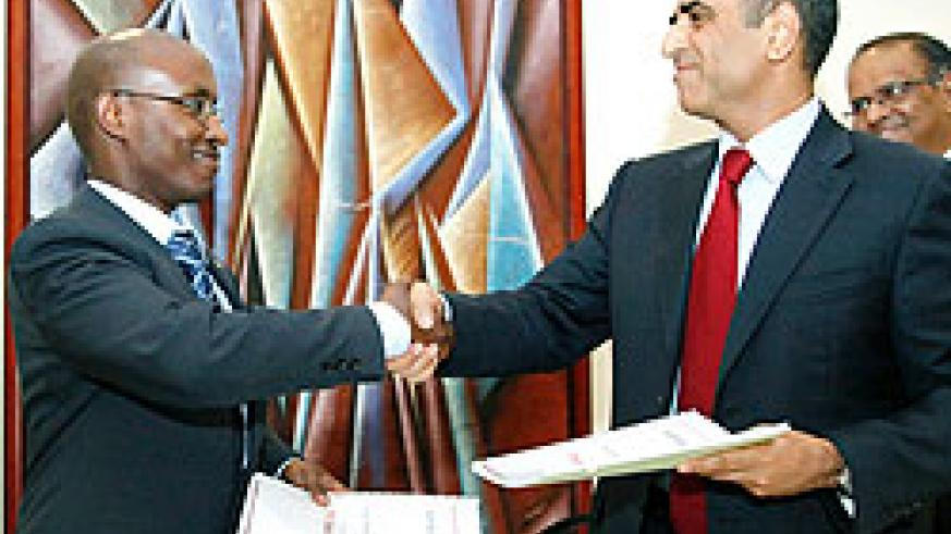 ICT Minister Dr Ignace Gatare (L), exchange documents with Sunil Bharti the managing director of Bharti Airtel as the latter formally entered the Rwandan market. The New Times / File.