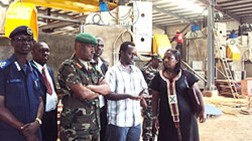 Eng.Dominique Rwizinkindi  (2L) showing Eastern province Governor (R) some parts of the granite factory as security officials look on. The New Times / D. Ngabonziza.