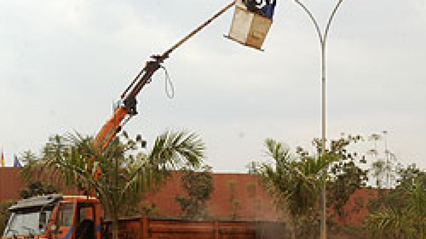 Kigali City Council employees mount streetlights in Kigali City. The New Times / File.