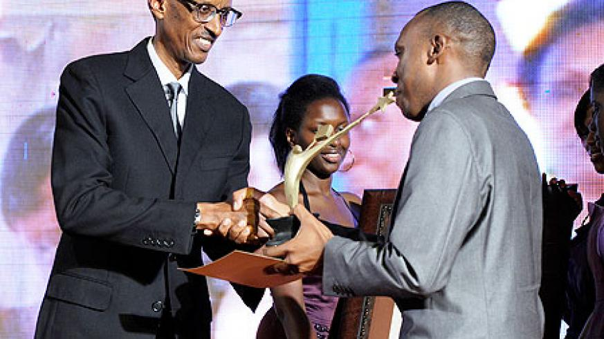 President Kagame presents an award to one of the young achievers in Kampala, yesterday. The New Times/Village Urugwiro.