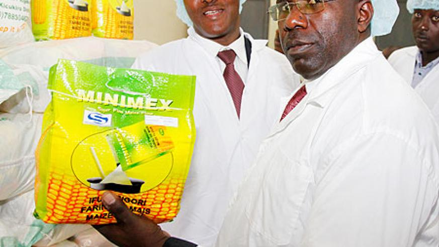 Prime Minister Habumuremyi  inspects maize flour manufactured by Minimex  during his tour of the plant yesterday. The New Times / T. Kisambira