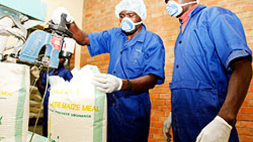 Workers package flour at local milling firm MINIMEX. The milling company currently purchases maize from Tanzania. The New Times / Timothy Kisambira.