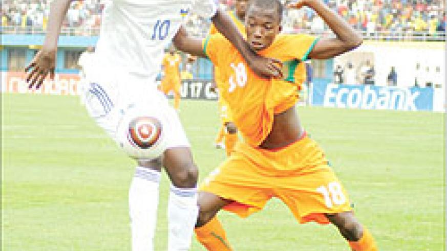 Andrew Buteera (L) shields the ball from an Ivory Coast player in the Caf U-17 Championship early this year. The Amavubi midfielder is expected to go under the knife this month. The New Times / File.