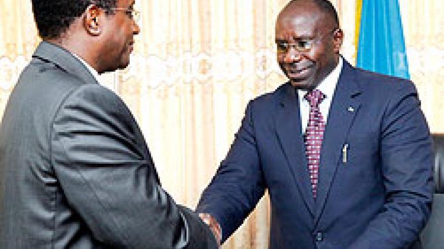 Dr. Vincent Biruta(L) minister of Education, receiving documents from Prime Minister Pierre Damien Habumuremyi.  The New Times / T. Kisambara.