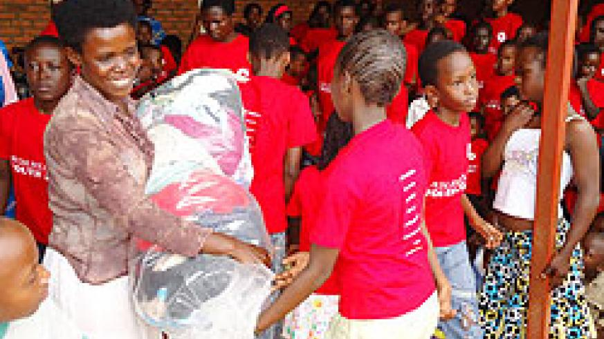 One of the beneficaries happily recieves her package .The New Times / G. Mugoya