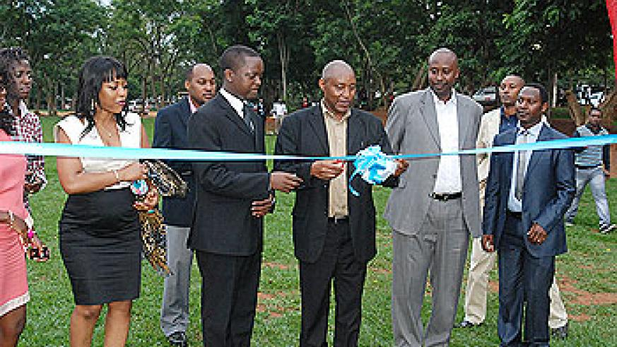 The former Headmaster of RIA Peter Claver Nkurunziza cuts the ribbon. Looking on are some of the OBs and OGs of RIA. The New Times/Courtesy photos.