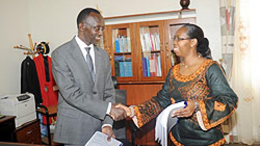 Former Chief Justice Aloysia Cyanzayire (R) hands over to her successor Sam Rugege yesterday. The New Times / J. Mbanda.