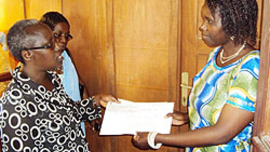 Josephine Uwamariya, ActionAid country director (left) hands over checque of the women's grant to Josephine Uwantege in charge of social affairs at Rwabicuma Sector. The New Times / Courtesy