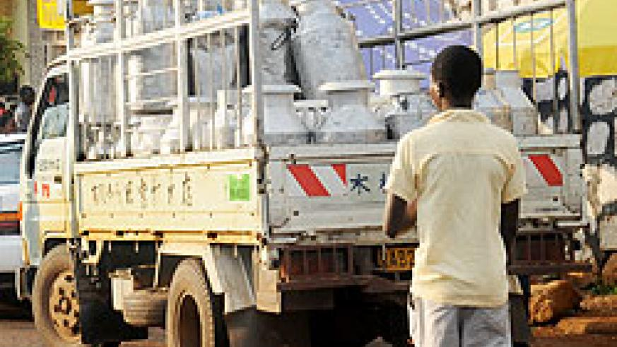 A boy loads milk cans. The New Times / File.