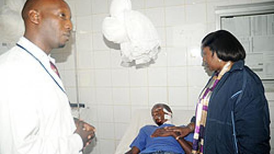 Health Minister Dr Agnes Binagwaho with one of the grenade explosion victims at Kibagabaga Hospital. Left is the Hospital's director Dr Christian Ntizimira. The New Times / J. Mbanda