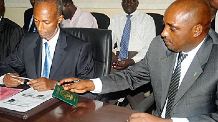 Director General of Immigration and Emigration Anaclet Kalibata (L) and National ID Coordinator Pascal Nyamulinda examine the new travel document at its launch on Tuesday. The New Times / File