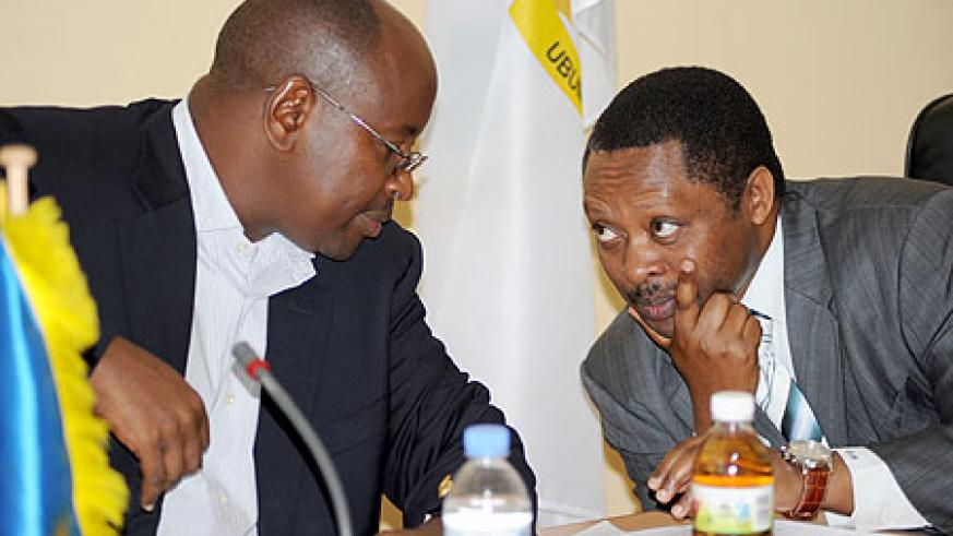 Local Government Minister James Musoni (L), and the CEO of Rwanda Governance Board, Prof. Anastase Shyaka, consult at a news conference yesterday. The New Times / John Mbanda.