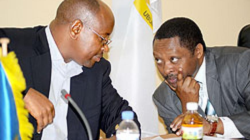 Local Government Minister James Musoni (L), and the CEO of Rwanda Governance Board, Prof. Anastase Shyaka, consult at a news conference. The New Times/John Mbanda.