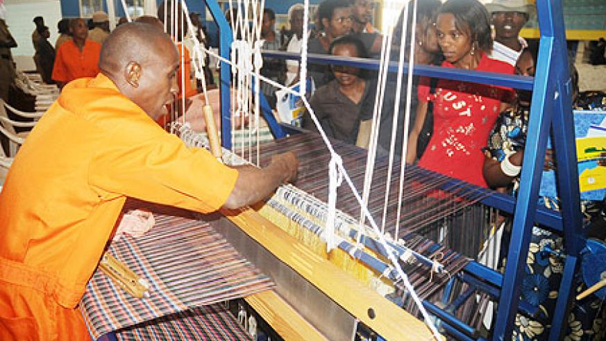 A prisoner makes a fabric during an  Open Day organised by   Ministry of Internal Security, at  Petit Stadium, Remera, yesterday. The New Times / J. Mbanda.