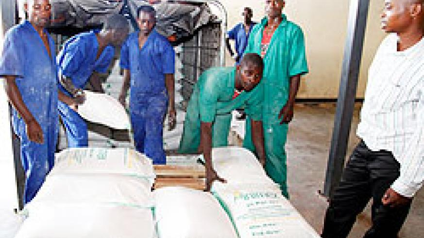 MINIMEX employees  load sacks of maize flour milled at the company. A new firm  has been established with the responsibility of trading grains and cereals. The New Times / File.