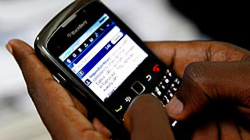 A tweep uses his Blackberry to share his views with the world. The New Times / T. Kisambira.