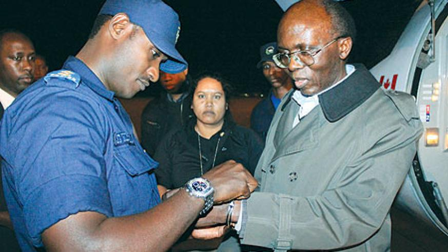 Léon Mugesera being handcuffed upon arrival at Kigali International Airport last night. The New Times / Timothy Kisambira.