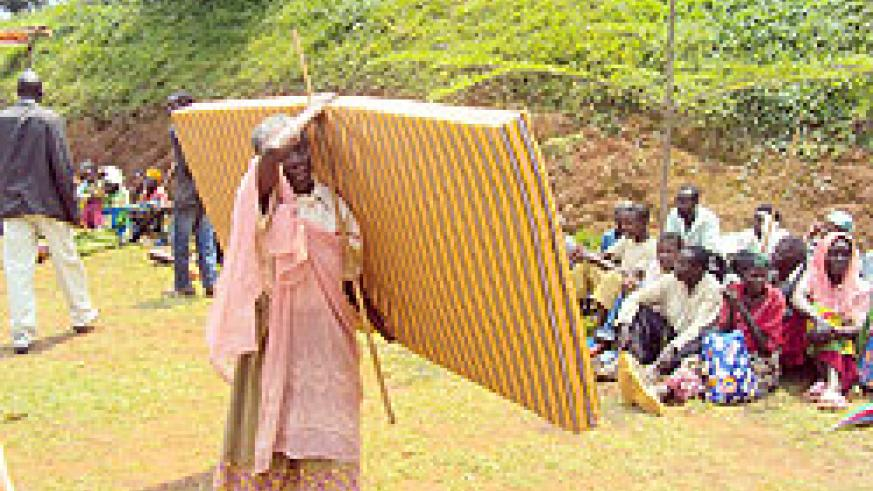 An elderly woman collects a mattress during an event organised to support the most vulnerable. The New Times/J.P Bucyensenge.