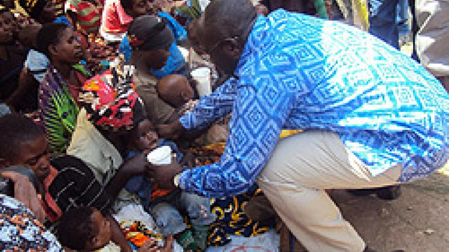 PM Habumuremyi offers milk  to  a child, kick starting the  national campaign against malnutrition. The New Times  JP Bucyensenge