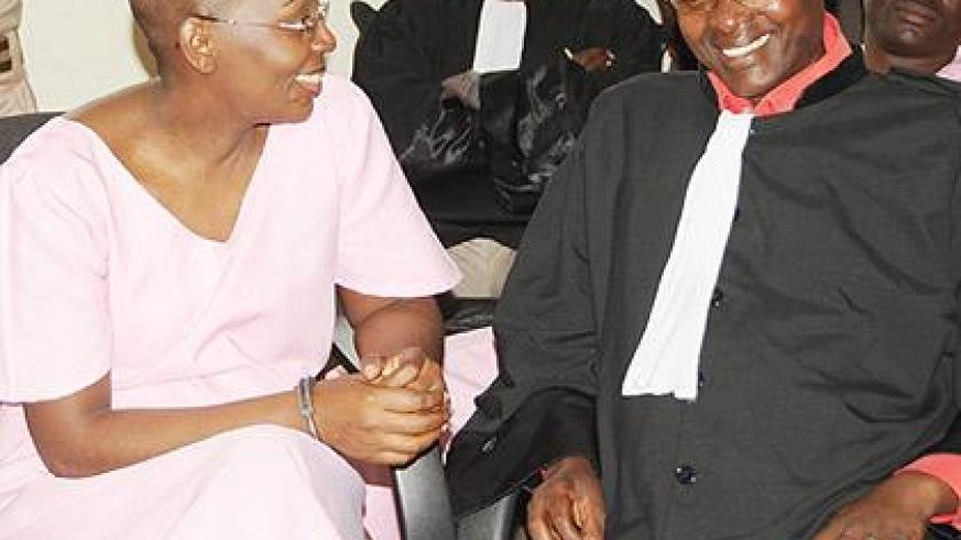 Victoire Ingabire sharing a light moment with her lawyer Gatera Gashabana as she appeared before court. The New Times / file