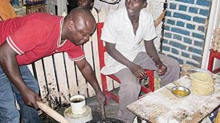 The writer tries out his cooking skills at Mama Uwera's roadside eatery