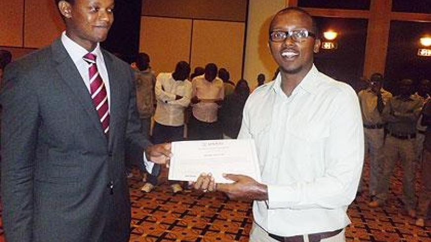 The Chairman of the Tourism Chamber at PSF, Edwin Sabuhoro (L)  handing a certificate to one of the trainees, Bilima Innocent. The NewTimes / Grace Mugoya.