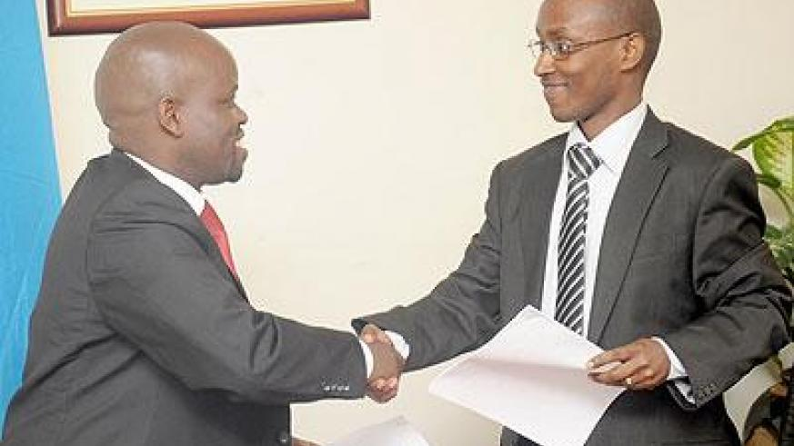 Minister of Youth Jean Philbert Nsengimana (L) and Ignace Gatare shake hands at the handover ceremony on Tuesday following the transfer of ICT portfolio to the Ministry of Youth. The Sunday Times/ John Mbanda