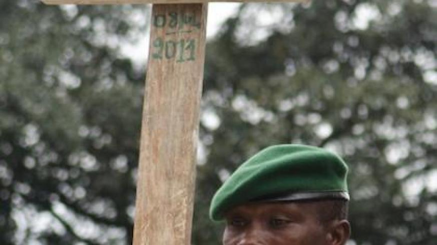A Congolese ranger holds the grave cross for a colleague killed in an attack by FDLR last year. Net photo.