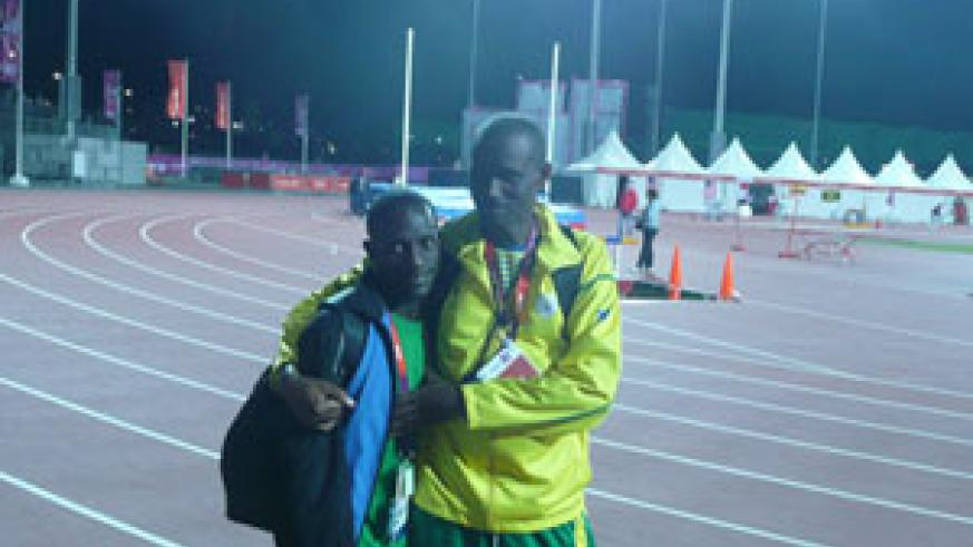 Robert Kajuga and his coach Innocent Rwabuhihi enjoy the moment after competing in the 10,000m men's final on Saturday night. Net photo.
